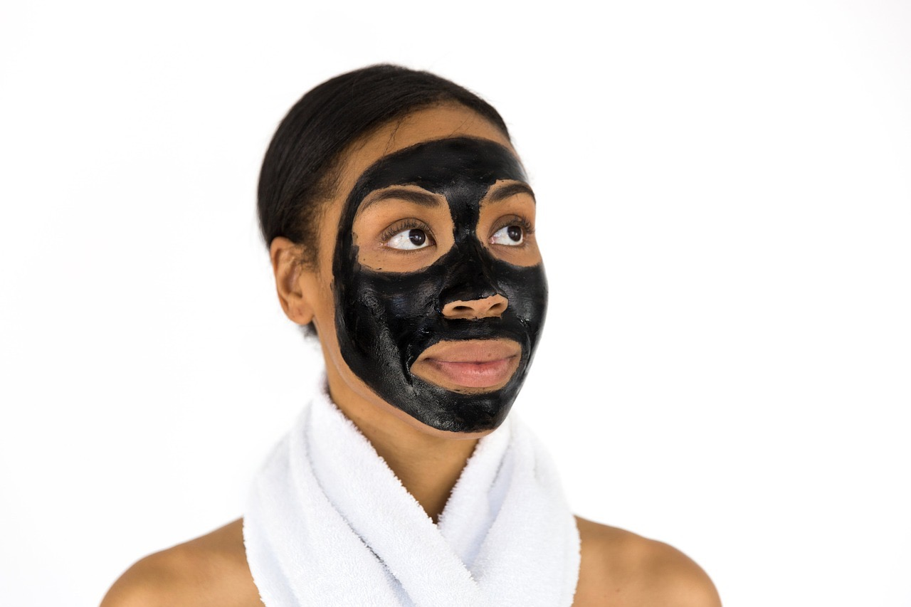 female rejuvenating her skin with black mask
